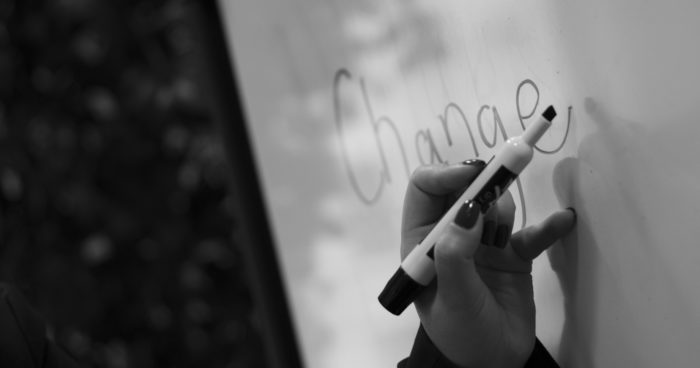 """The word """"change"""" written on a whiteboard with a handheld marker"""